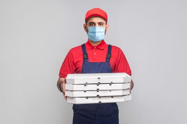検疫での配達。青いユニフォームと赤いtシャツを着た外科用医療マスクを持った若い男が、灰色の背景に段ボールのピザボックスのスタックを立って保持しています。屋内、スタジオショット、孤立、
