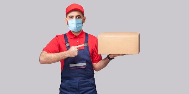 検疫での配達。青いユニフォームと赤いtシャツを着た外科用医療マスクを持った若い男が立って、灰色の背景の段ボール箱に指を向けています。屋内、スタジオショット、孤立、