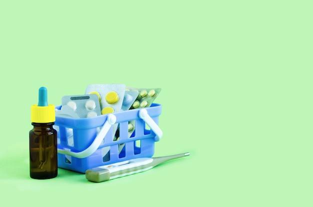 Доставка, покупка лекарств в аптеке онлайн, заказ на дом. таблетки в корзине на зеленом. лечение и профилактика covid