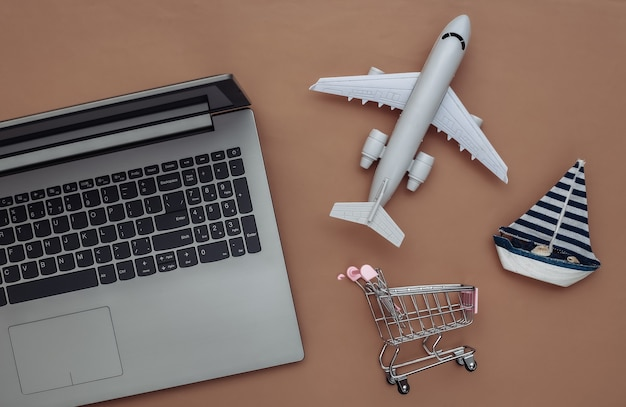 Delivery, online shopping. laptop and sailboat, shopping trolley, air plane on brown background. top view. flat lay
