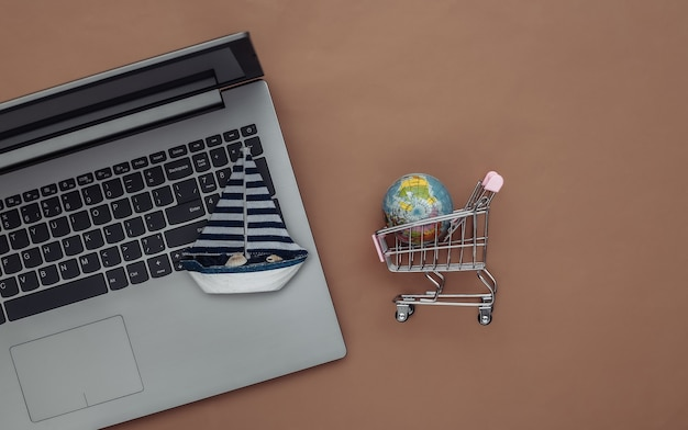 Delivery, online shopping. laptop and sailboat, shopping trolley with globe on brown background. top view. flat lay