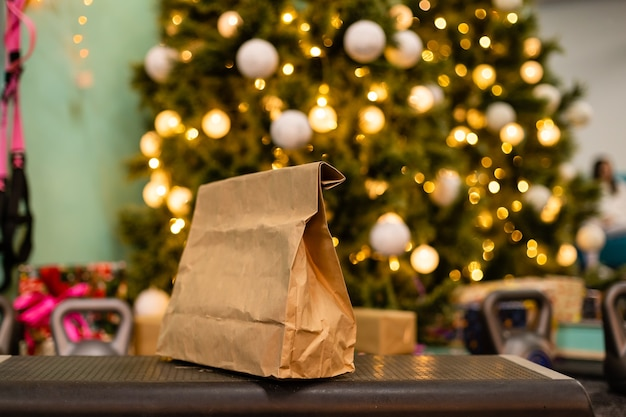クリスマスツリーの背景に健康的な食品、体重、ダンベルの配信パッケージ