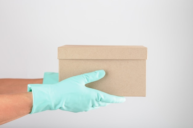 Delivery of a parcel with gloves for protection against viruses and diseases on a white background.