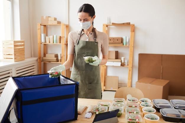 Доставщик в защитной маске упаковочные коробки со свежими овощами в сумку для доставки