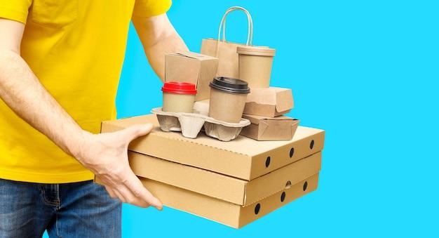 黄色いシャツの配達員は、さまざまな持ち帰り用の食品容器、ピザボックス、ホルダーに入ったコーヒーカップ、青い背景の紙袋を持っています。コピースペース