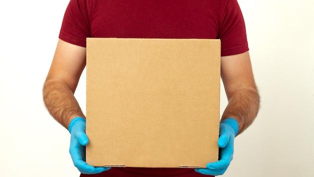 宅配ピザ。医療用ゴム手袋とマスクで段ボール箱を保持している配達人。コピースペース。高速で無料の配達輸送。