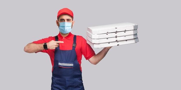 検疫でピザを配達します。青いユニフォームと赤いtシャツを着た外科用医療マスクを持った若い男が立って、灰色の背景に段ボールのピザボックスのスタックに指を持って指しています。