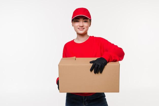 赤い帽子をかぶったパッケージを保持し、配達する配達郵便サービスアジアの女性