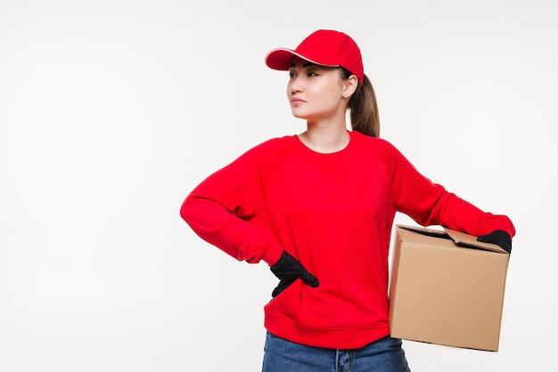 Donna asiatica di servizio postale di consegna che tiene e che consegna il pacchetto che porta il cappuccio rosso