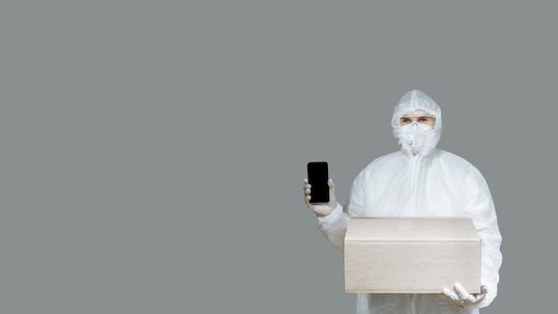 Delivery to quarantine. man with a surgical medical mask, gloves and a protective hazmat suit holding a cardboard box and showing a smartphone display on a gray