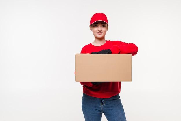 配達、移転、開梱。白い壁で隔離の段ボール箱を保持している若い女性の笑顔