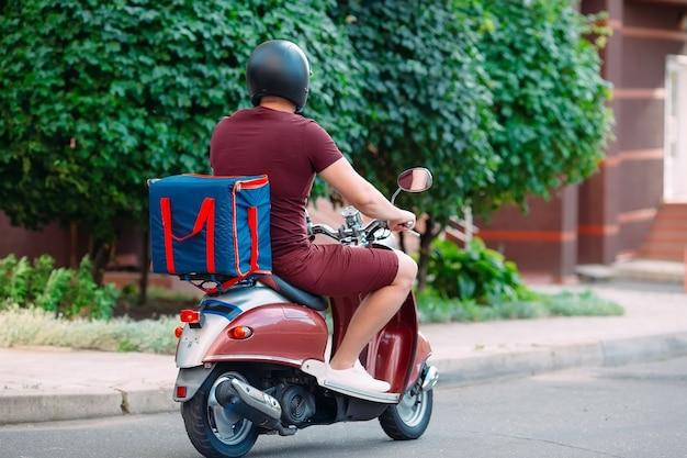 Всадник доставки со скутером в передней части дома