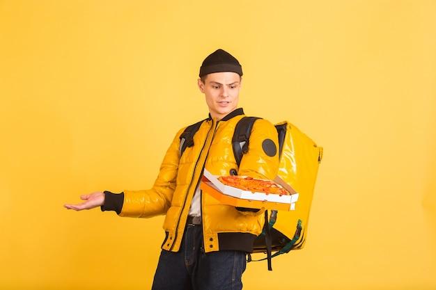 配送サービスのコンセプト。男は黄色の壁に隔離された食品や買い物袋を配達します
