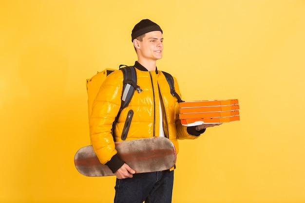 Concetto di servizio di consegna. l'uomo consegna cibo e borse della spesa isolati su muro giallo