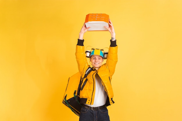 Delivery service concept. man delivers food and shopping bags isolated on yellow wall