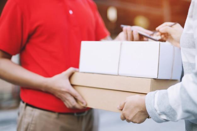 手に箱を持って家のドアベルを鳴らしている配達サービスの宅配便