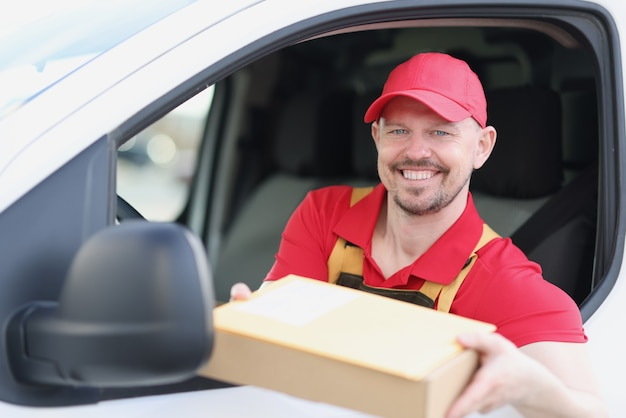 Delivery service driver offers package from his van