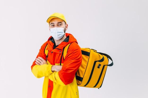 黄色い帽子をかぶった配達サービスの従業員は、検疫 covid19 での均一なサーマル フード バッグ バックパックの仕事の宅配便サービス