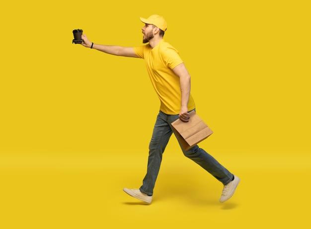 配達サービス、ファーストフードと人々のコンセプト-コーヒーと使い捨ての紙袋を持つ幸せな男。