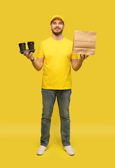 Delivery service, fast food and people concept - happy man with coffee and disposable paper bag.