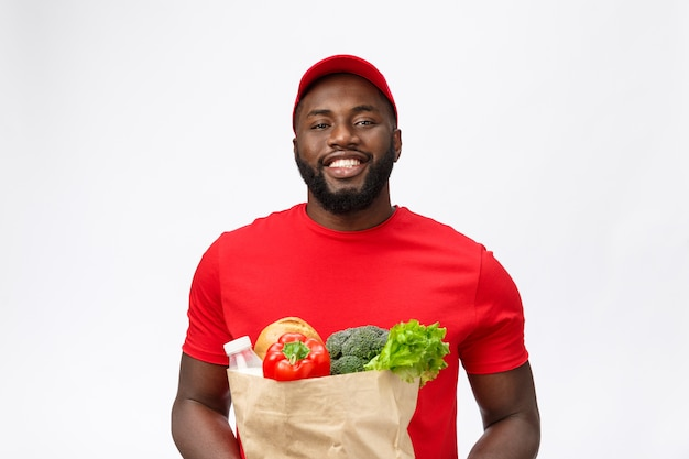 Delivery service - handsome african american delivery man carrying package grocery food and drink from store.