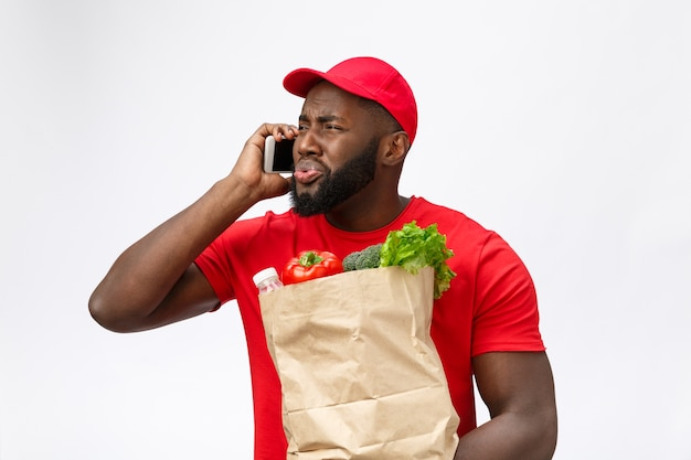 Delivery service: handsome african delivery man talking to mobile with shocking facial expression.