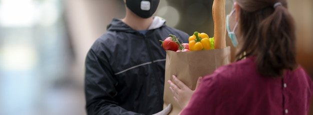 Delivery service man handing over fresh food bag to female customer