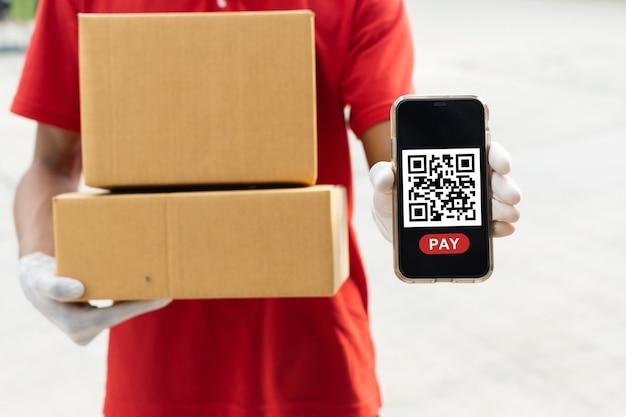 고객이 집에서 온라인 결제, 빠른 배달 서비스, 속달 배달, 온라인 쇼핑 개념을 위해 휴대폰에서 qr 코드를 스캔하기를 기다리는 소포 우편함을 들고 있는 배달 서비스 남자