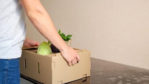 配達サービスの男性は、白い背景の側面図のクローズアップに対して灰色のテーブルに野菜の段ボール箱を置きます