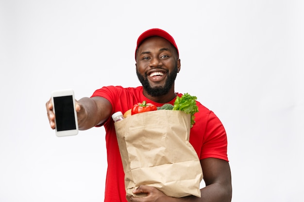 Delivery service - portrait of handsome african american delivery man or courier showing mobile phone on you to check the order.