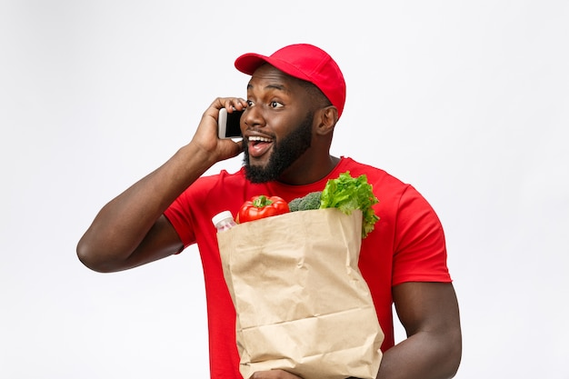 Delivery service - portrait of handsome african american delivery man or courier with grocery package and talking on mobile phone to check the order.