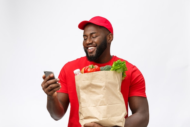 Delivery service - portrait of handsome african american delivery man or courier with grocery package and using mobile phone to check the order.