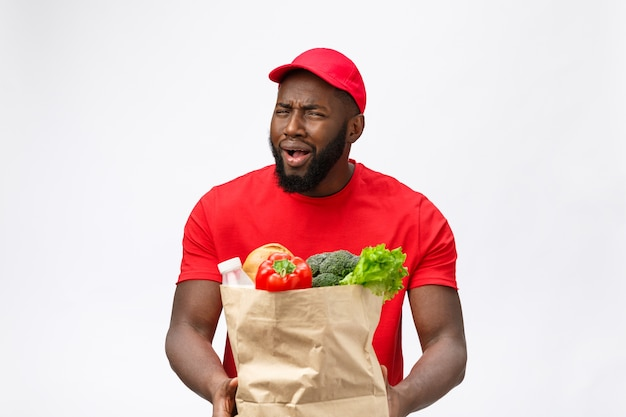 Delivery service - portrait of serious african american delivery man holding grocery bag