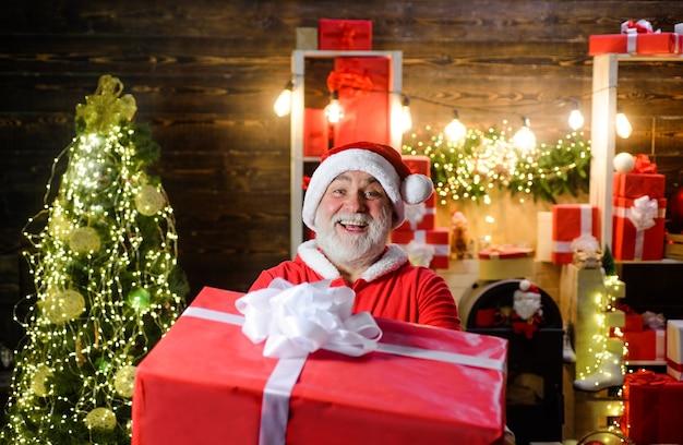 Служба доставки санта клаус с большой подарочной коробкой бородатый мужчина в костюме санта с рождественским подарком
