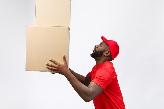 Служба доставки - вид сбоку портрет счастливого афро-американского доставщика в красной ткани, держащего пакет коробки.