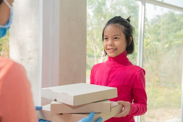 Delivery service in t-shirt, in protective mask and gloves giving food order, holding three pizza boxes in front house, woman accepting delivery of boxes from delivery man during covid-19 outbreak.