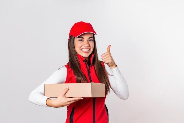 白い背景で隔離赤い制服を着た笑顔の女性を配信します。