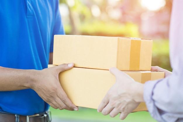 Сотрудники службы доставки несут бумажные коробки.