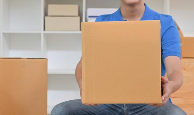 茶色の紙箱を持って配達スタッフ。