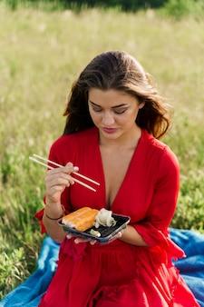 소녀를위한 상자에 배달 초밥 세트. 녹색 공원에서 빨간 드레스 좌석에 매력적인 여자와 초밥을 먹는다. 소셜 네트워크 용 세로 사진은 레스토랑 용 광고