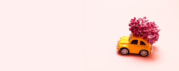 Delivery . toy yellow car with lilac flower branch on a pink simple background with place for text.
