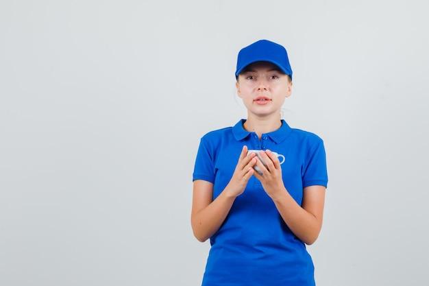Donna di consegna in maglietta blu e cappuccio che tiene tazza di bevanda