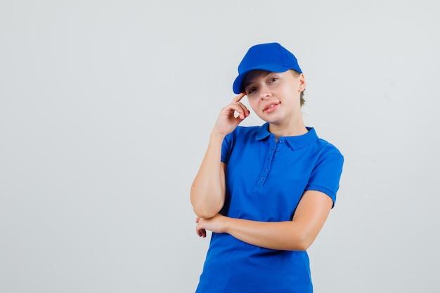 Donna delle consegne in maglietta blu e cappuccio che si appoggia alle tempie sul dito e sembra speranzosa