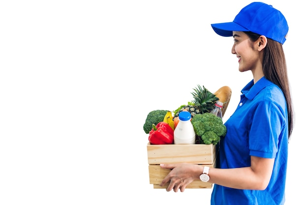 Delivery woman in blue uniform carrying package of grocery food with vegetable and fruit on white background