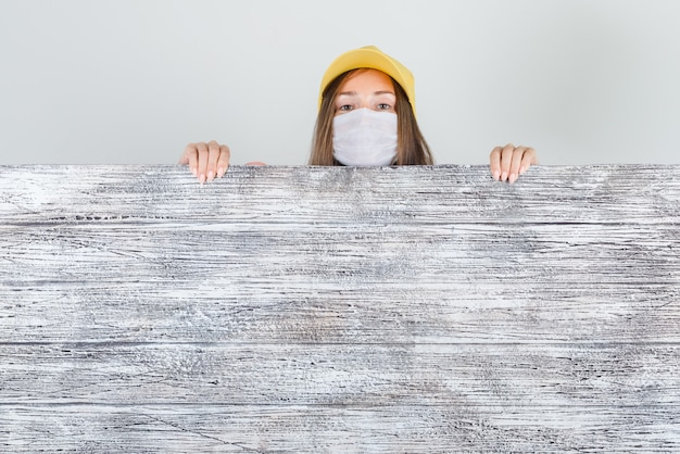Delivery woman in cap, mask peeking behind wooden board