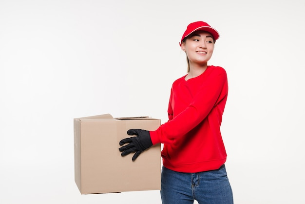 Женщина доставки, несущая картонную коробку, изолированную на белом