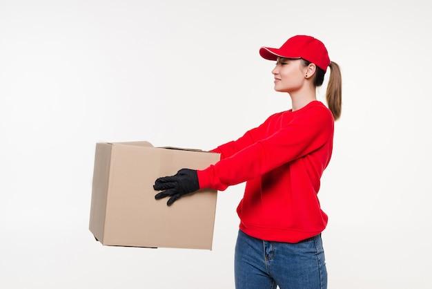 Женщина доставки, несущая картонную коробку изолирована