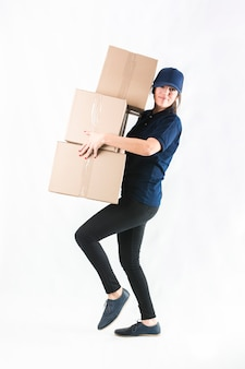 Delivery woman carrying stacked of courier boxes against white background