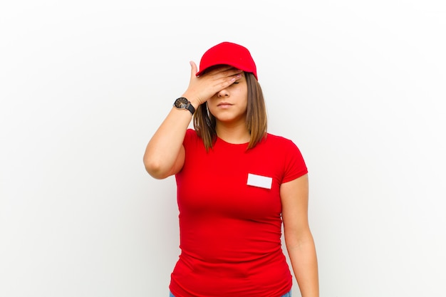 Delivery woman covering eyes with one hand feeling scared or anxious, wondering or blindly waiting for a surprise against white