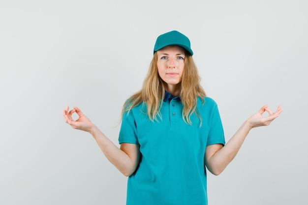 Donna di consegna che fa meditazione in maglietta, cappello e che sembra pacifica